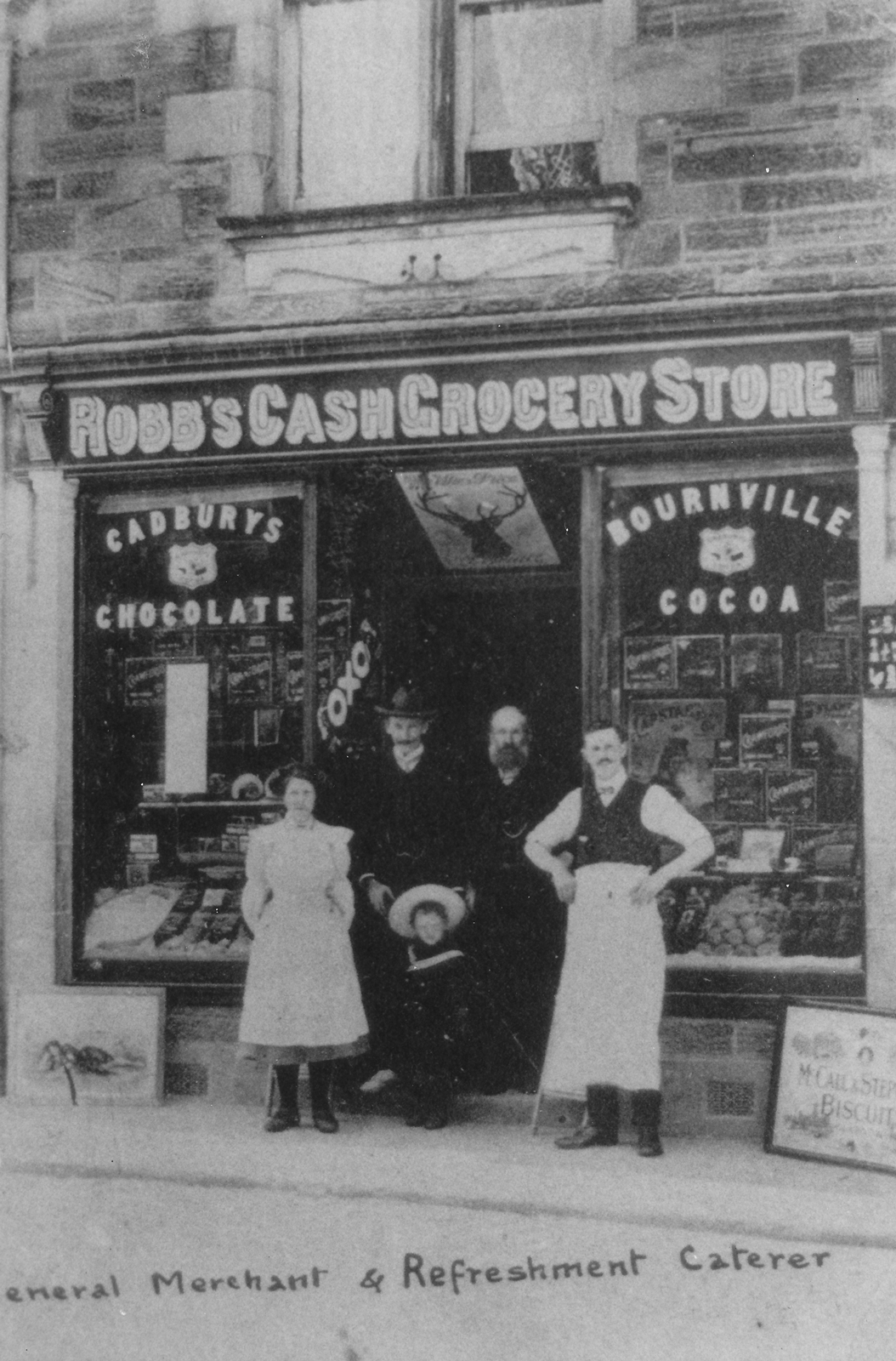 Archive photograph of 3 men, a young lady and child standing in the doorway of Robbs Cash Grocery Store